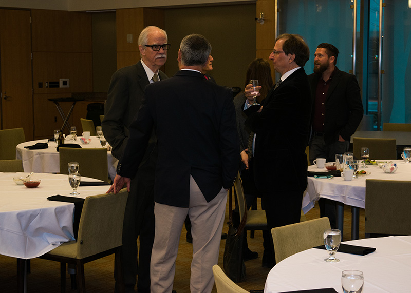 Keynote speaker Dr. Larry Pickering speaks with colleagues at the Secchia Center